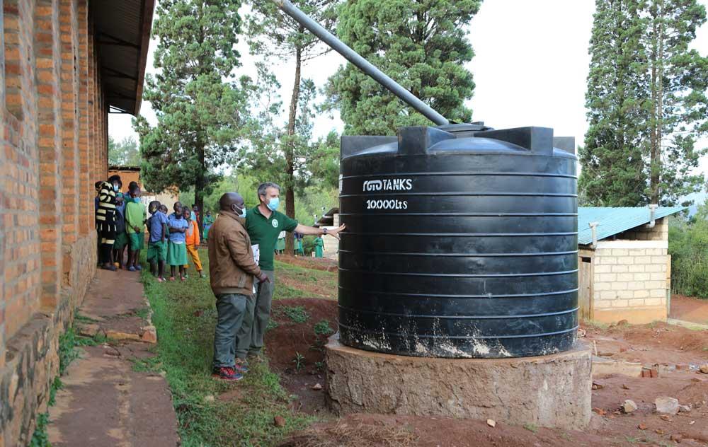 Le système de récupération d'eau de pluie et une des citernes de 10 000 litres. Les latrines en arrière plan